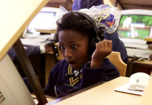 Eight year old Jenni-Lee Mason stares in awe as she uses a computer for the first time at a township school in Cape Town, South Africa. (Reuters)