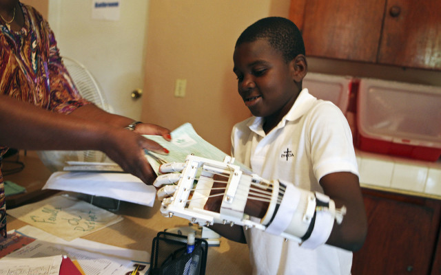 Handicapped Haitian boy Stevenson Joseph learns to use a 3D-printed prosthetic hand at the orphanage where he lives in Santo, near Port-au-Prince, April 28, 2014. (Reuters)