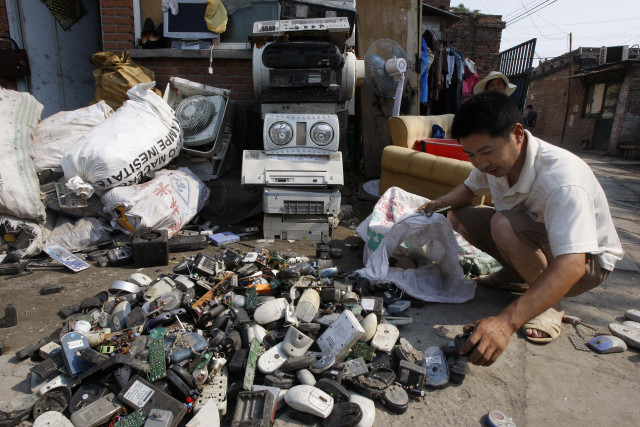 FILE - A man sorts through computer parts and phone chargers at a recycling village in Beijing. (AP)