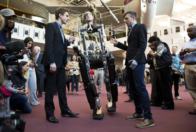 "Dr. Bertholt Meyer (R) and James Pope assist the robot, ""The Incredible Bionic Man,"" while it walks at the Smithsonian National Air and Space Museum in Washington. (Reuters)"