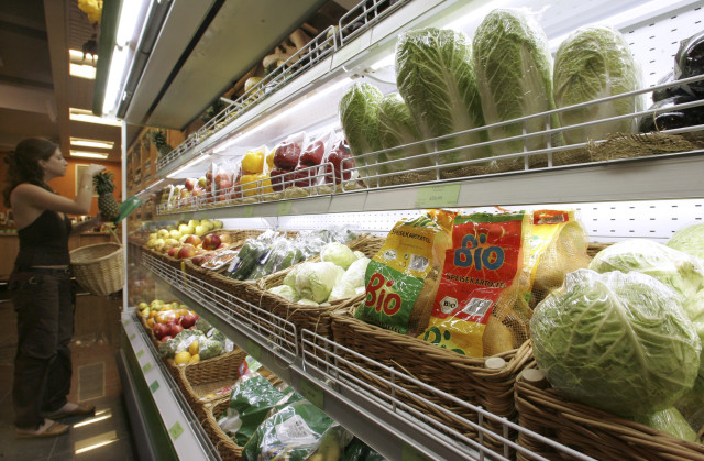 A customer stands in a supermarket as a label of GM-free food is seen in the foreground in Moscow, Russia, June 22, 2007. (Reuters)