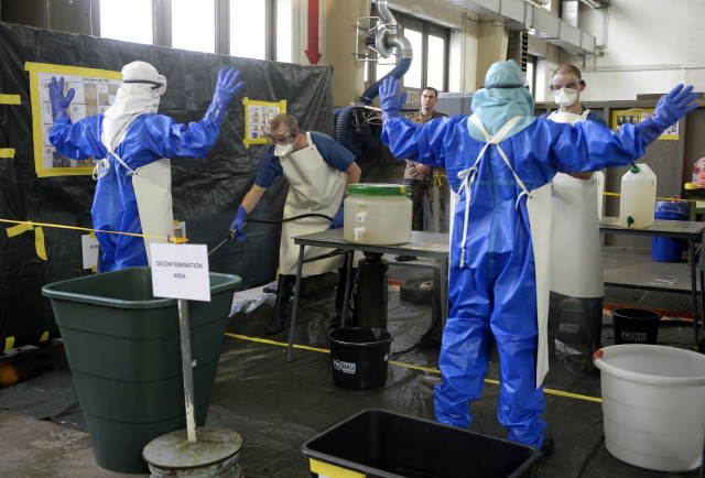 Volunteers of German army Bundeswehr, wearing protective suits, are decontaminated during an Ebola training session at the Marseille barracks in Appen, Oct. 23, 2014. (Reuters)