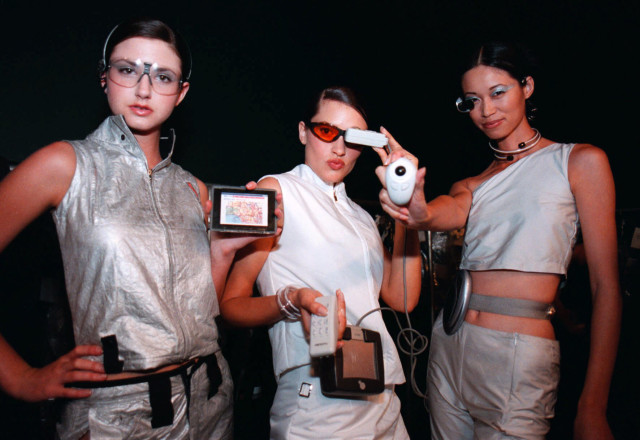 """Models display a wireless mini-computers and other high tech gadgets, June 14, 2000, during the """"Brave New Unwired World"""" fashion show at Bravo! located in downtown Minneapolis. (AP)"""