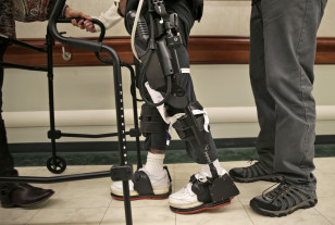 James Cody (C) walks with the aid of a bionic exoskeleton and physical therapists at the Burke Rehabilitation Center in White Plains, N.Y., Nov. 10, 2014. (AP)