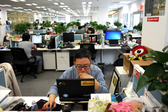 A picture taken April 16, 2014 shows a man using a laptop at an office of Sina Weibo, widely known as China's version of Twitter, in Beijing. (AFP)