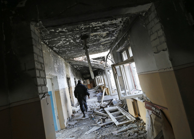 A man walks through a passageway of a mental hospital destroyed during heavy fighting between Ukrainian army and pro-Russian rebels in June in the village of Semyonovka, near the eastern Ukrainian city of Slaviansk, Sept. 28, 2014. (Reuters)