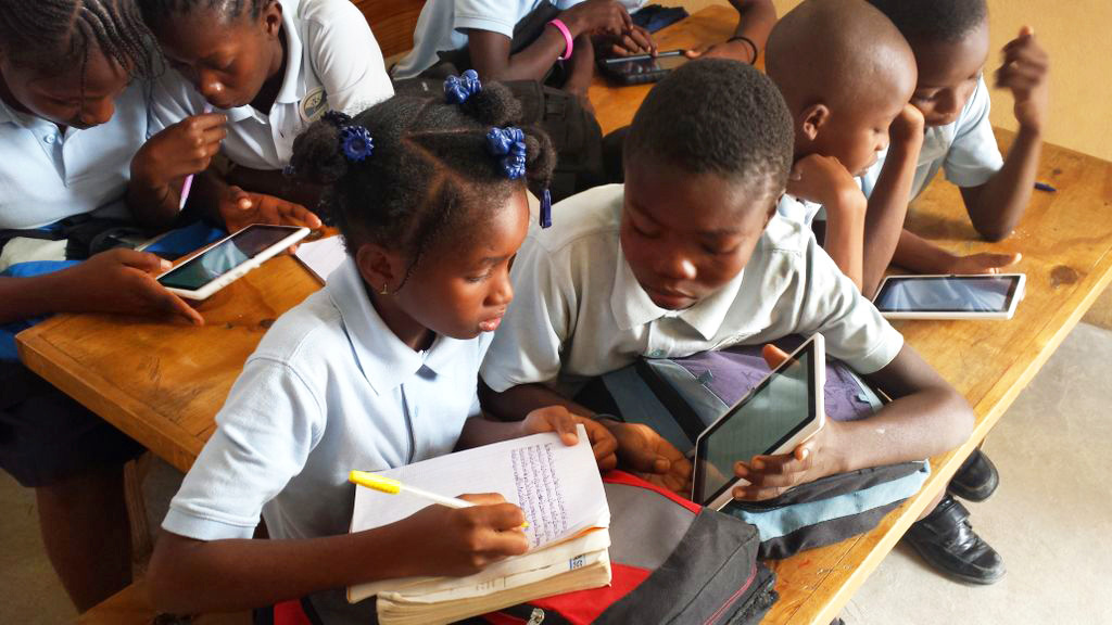 Two students at a school in Gressier, Haiti, who have a five-month library access, use the library in class for a lesson. (Maritza Chateau and Amanda Truxillo)