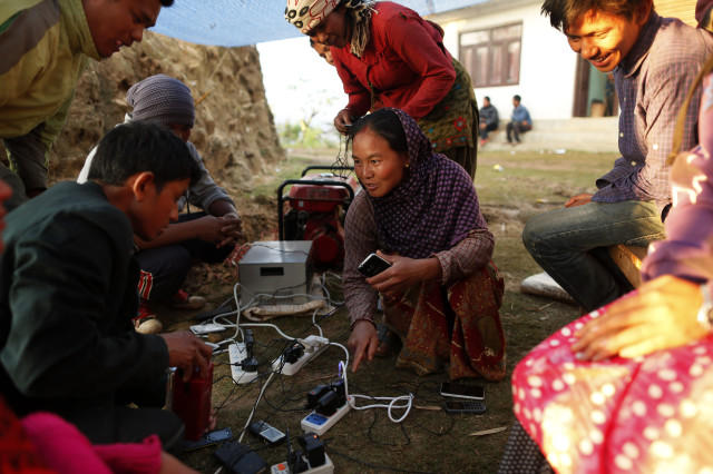 Young villagers charge their mobile phones from a generator in the destroyed village of Paslang near the epicenter of Saturday's massive earthquake in the Gorkha District of Nepal, April 28, 2015. (AP)