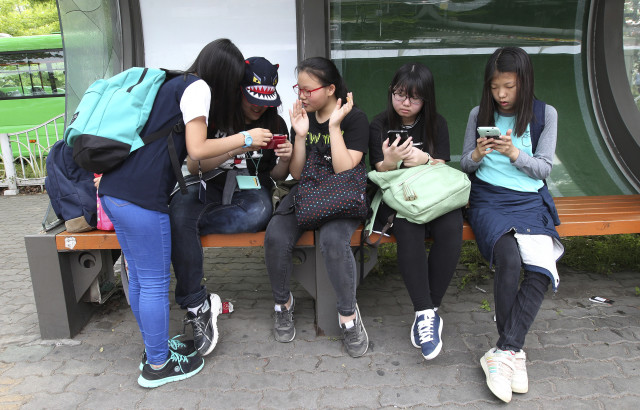 South Korean middle school students use their smartphones at a bus station in Seoul, South Korea, May 15, 2015. (AP)