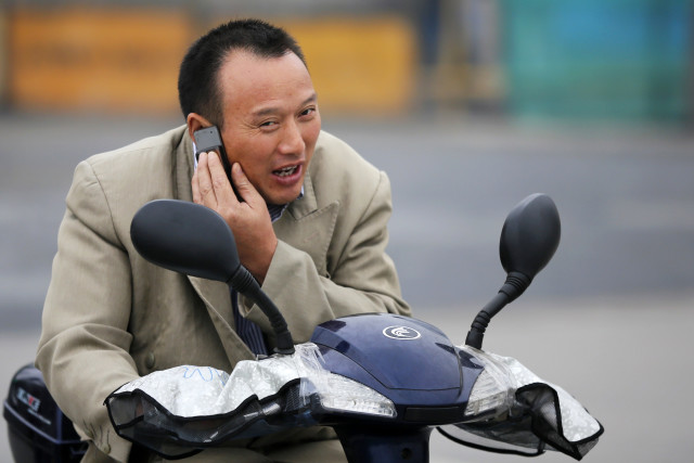 A man talks on his mobile phone as he drives an electric bike in Shanghai, China, Oct. 22, 2012. (Reuters)