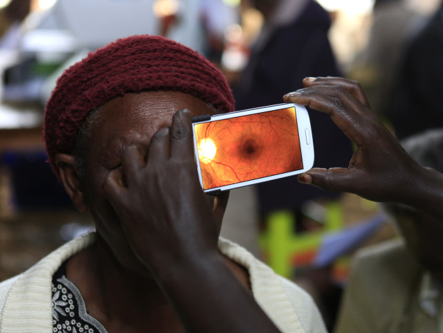 A woman undergoes an eye examination using of a smartphone at a temporary clinic by International Center for Eye Health at Olenguruone in the Mau Summit, west of Kenya's capital Nairobi, Oct. 29, 2013. (Reuters)