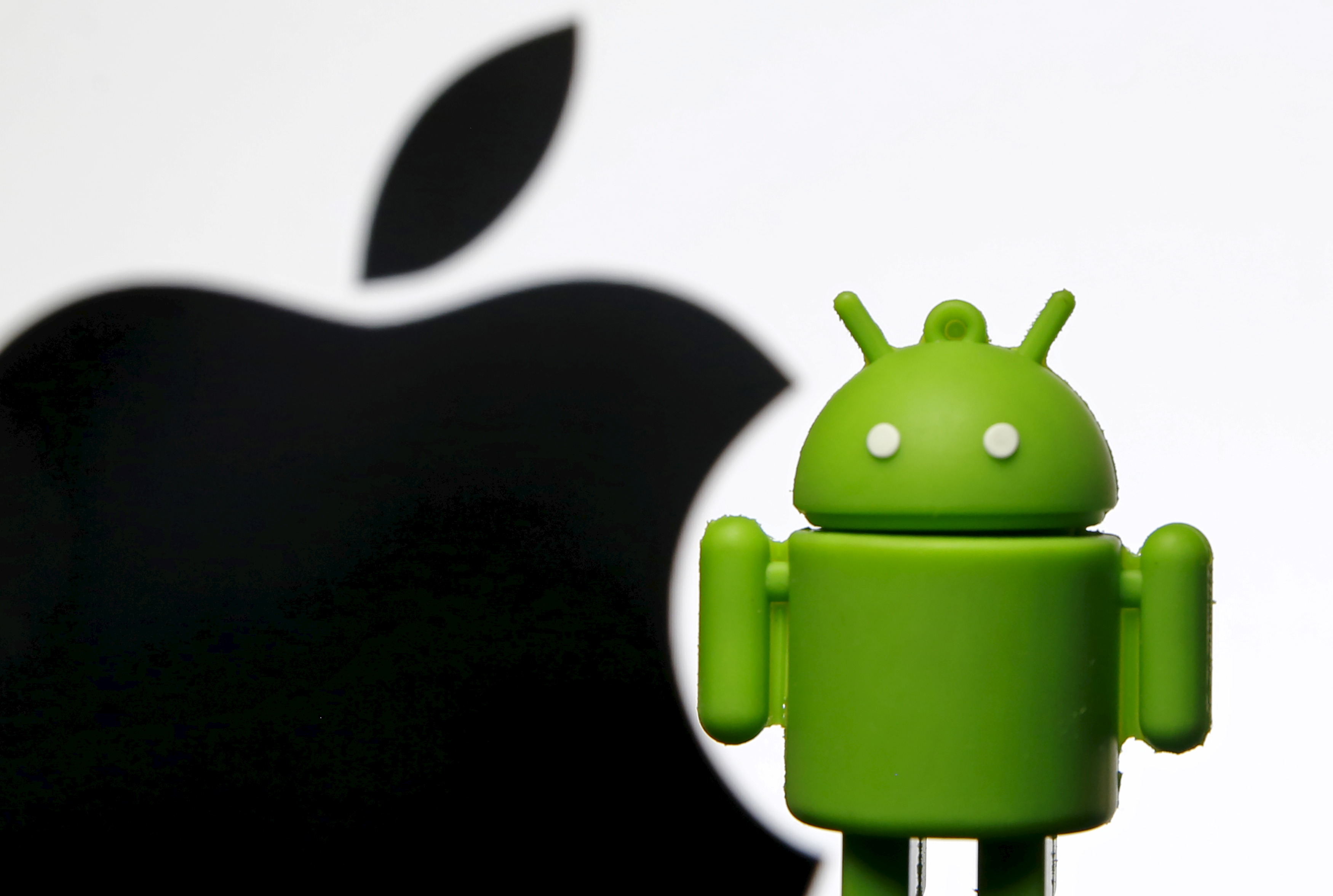An Android mascot is seen in front of a displayed logo of Apple in this illustration taken in Zenica, Bosnia and Herzegovina, May 5, 2015. (Reuters)