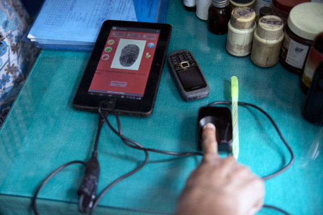 A tuberculosis patient scans his fingerprint into Operation ASHA's system to register his clinical visit and compliance with required treatments. (Prateek Ahuja)