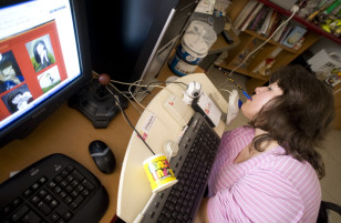 Macedonian Roza Mojsovska, who suffers from a rare disease that heavily limits the movement of her limbs, works on a computer with a pen in her mouth while moving the mouse with her chin, Bansko, east of the capital Skopje, May 23, 2008. (Reuters)