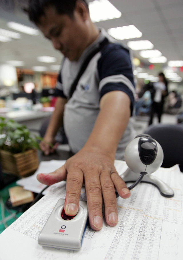 A man has his fingerprint scanned at a Taipei household registration office in Taiwan, June 17, 2005. (Reuters)