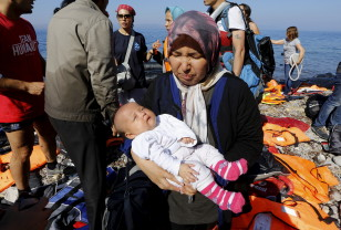 An Afghan refugee holds her three-month-old baby girl Zainab after arriving at a beach on the Greek island of Lesbos after crossing a part of the Aegean sea from Turkey Sept. 17, 2015. (Reuters)