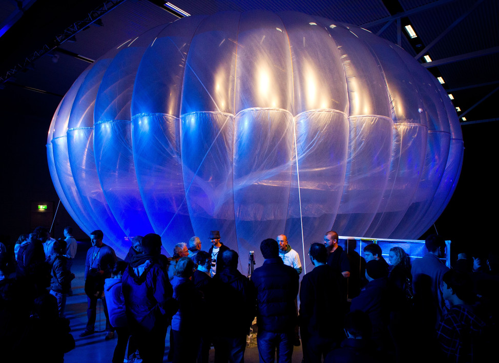 Visitors stand next to a high altitude WiFi internet hub, a Google Project Loon balloon, on display at the Airforce Museum in Christchurch, New Zealand, June 16, 2013.  Google hopes its balloons will bring Internet access to two-thirds of the world's population. (AFP)