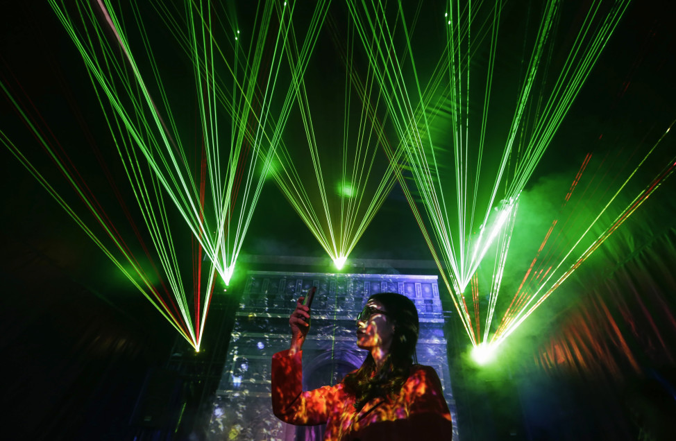A visitor takes pictures with her mobile phone in front of laser beams and a projected image of the Arc de Triomphe, in Wuhan, Hubei province, China, Nov. 2, 2013. (Reuters)