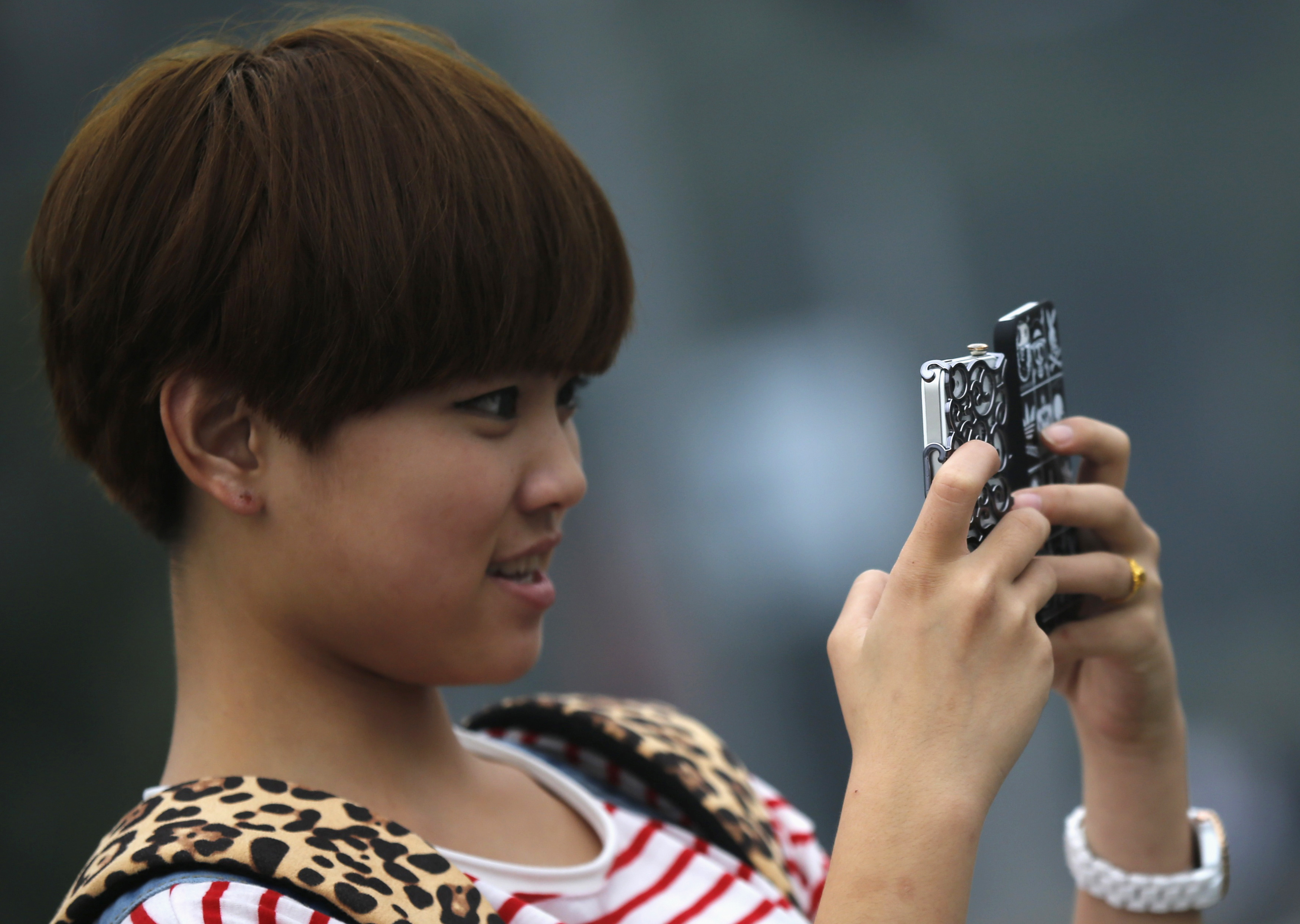 A young girl holds two mobile phones as she takes pictures at a downtown area of Shanghai, China, Oct. 22, 2012.
