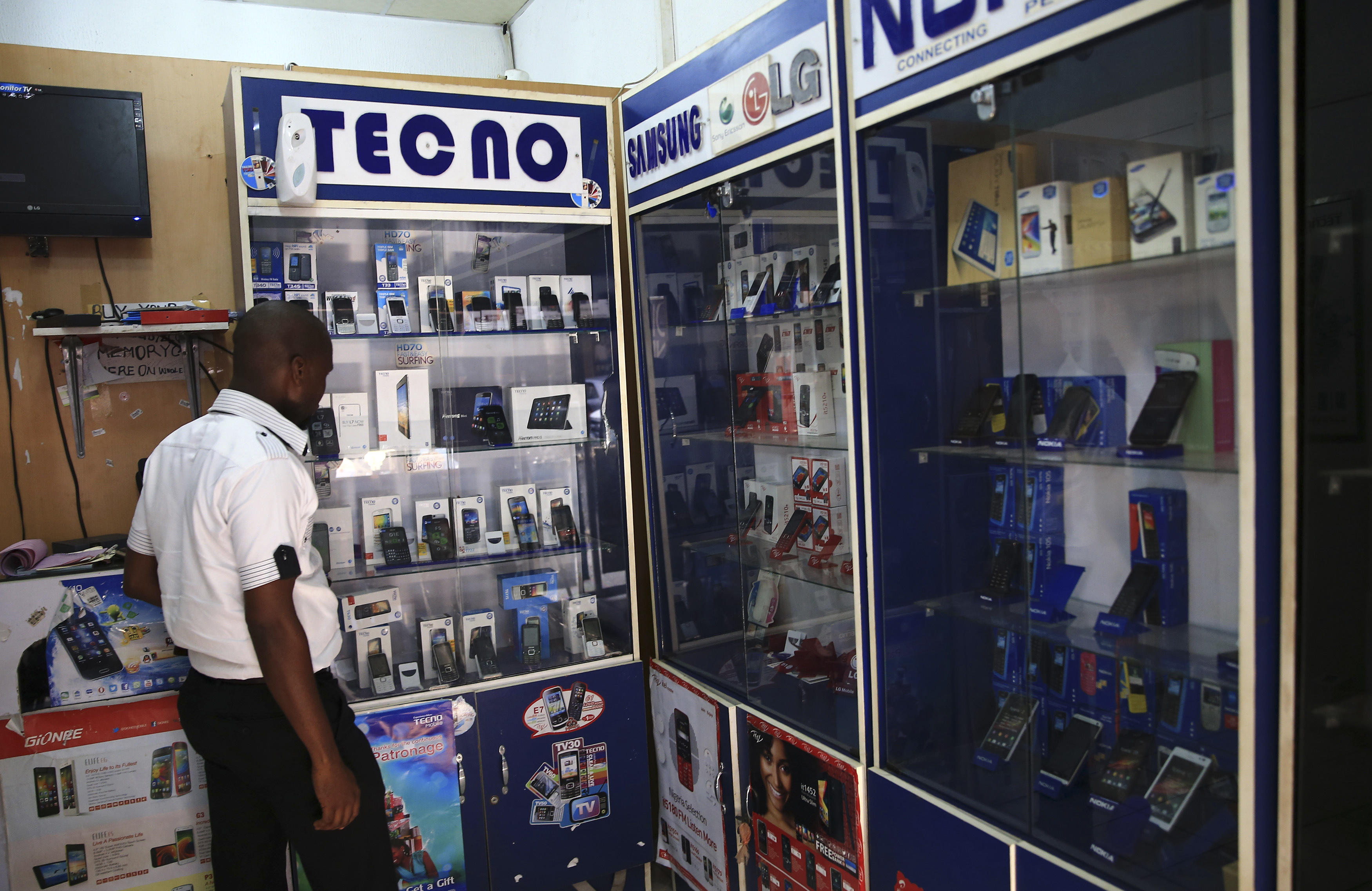 A man looks at smartphones on display at a shop at Wuse II business district in Abuja, Nigeria, Dec. 9, 2014. (Reuters)