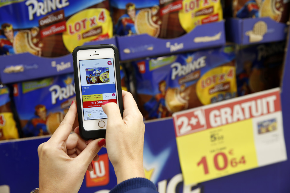 "A woman demonstrates the use of the application ""Promo C-Ou"" on her smartphone at the Carrefour supermarket in Lille"