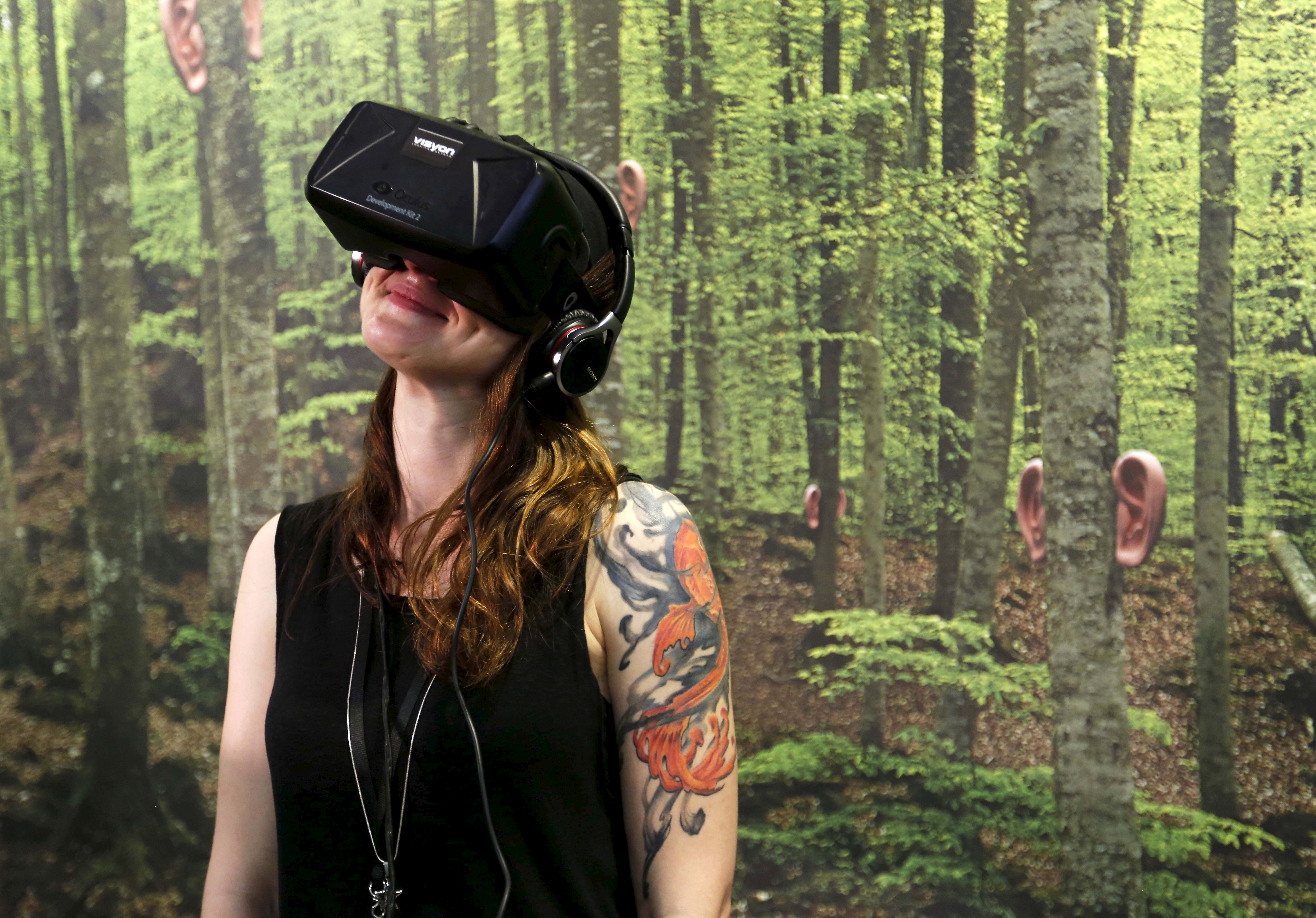 """A woman in Realities+D, a space for Virtual Reality content, smiles while watching virtual reality film """"Evolution of Verse"""" during the Sonar Festival in Barcelona, Spain, June 19, 2015."""