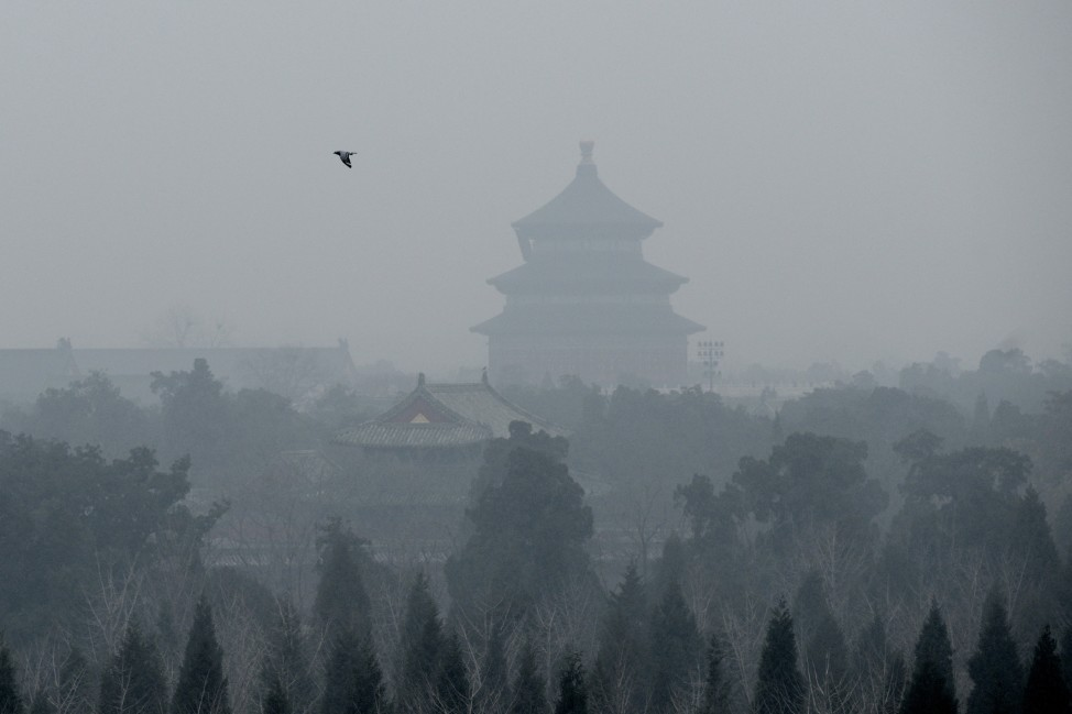 A bird flies over the grounds of the Temple of Heaven amid heavy air pollution in Beijing on Dec. 8, 2015. Half of Beijing's private cars were ordered off the streets on Dec. 8 and many construction sites and schools were closed under the Chinese capital's first-ever red alert for pollution. (AFP)