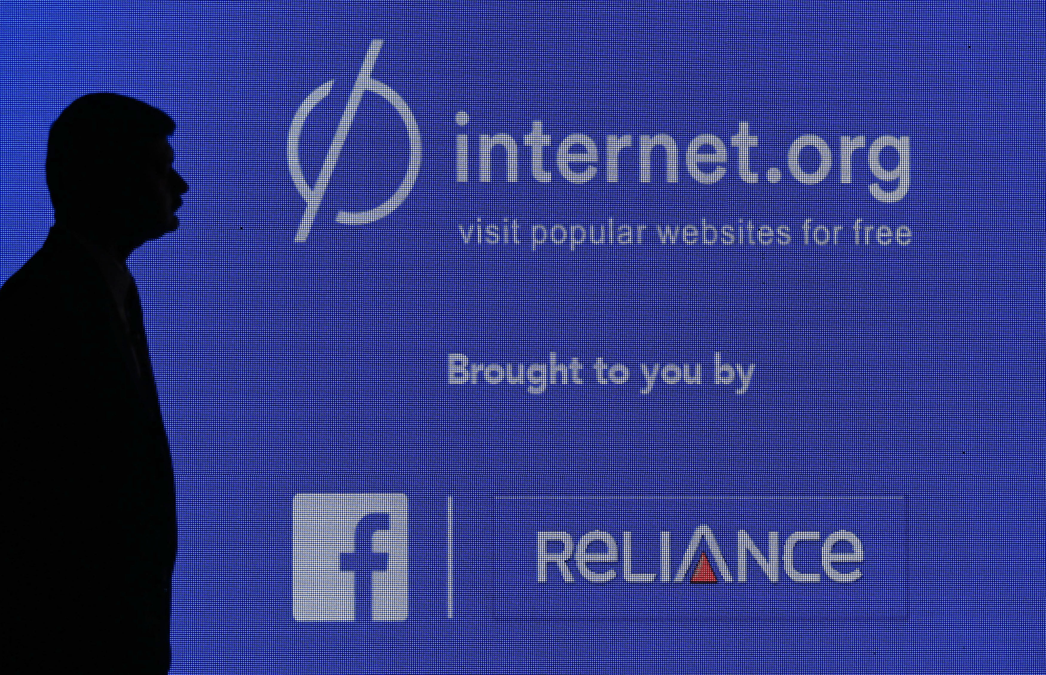 FILE - A staff member stands next to a display screen during a joint news conference by Reliance Communications Ltd. and Facebook Inc. in Mumbai, India, Feb. 10, 2015. (Reuters)