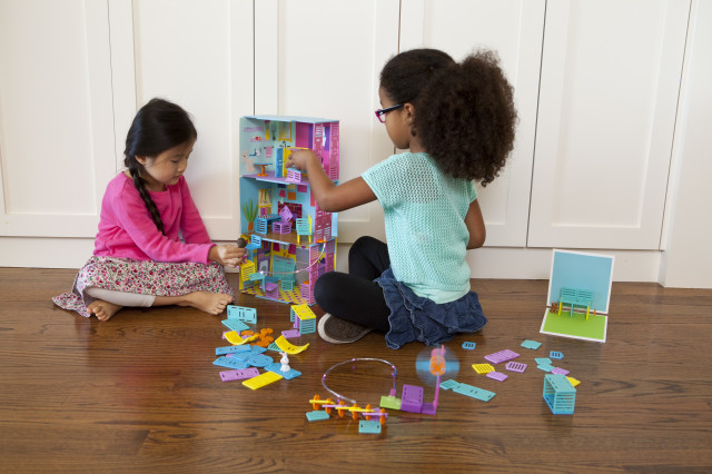 Isabella and Kira work together to complete their dollhouse, using Roominate bricks. (Roominate)