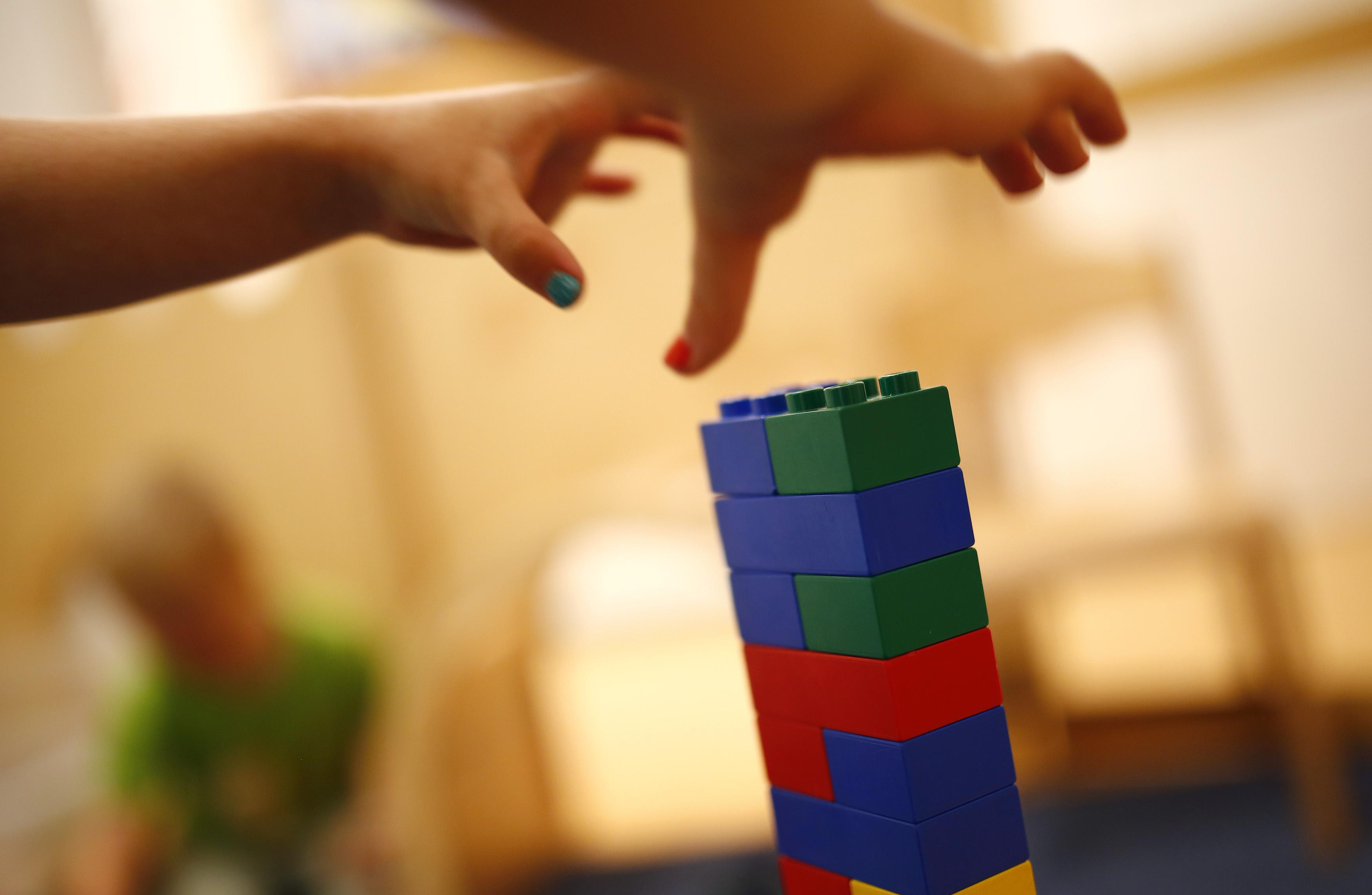 FILE - A child grabs LEGO bricks at a Kindergarten in Hanau, Germany, July 16, 2013. (Reuters)