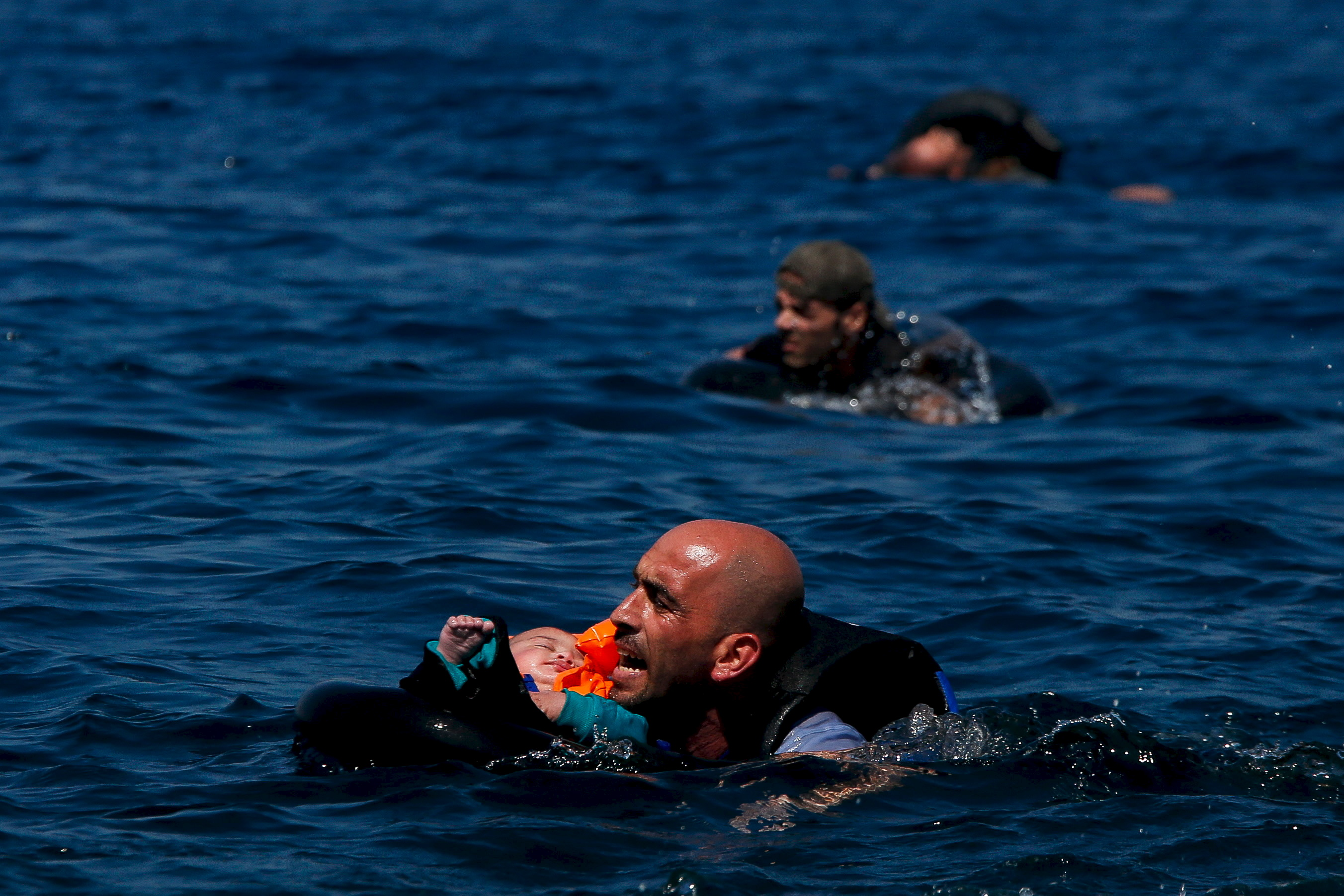 A Syrian refugee holding a baby swims towards the Greek island of Lesbos, Sept. 12, 2015, after another boat crammed with dozens of migrants and refugees deflated and sank. (Reuters)