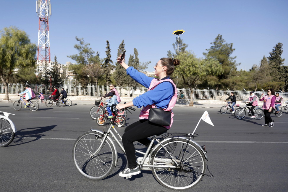 A woman takes a selfie while cycling along a street during a biking tour for charity, in Damascus, Dec. 11, 2015.