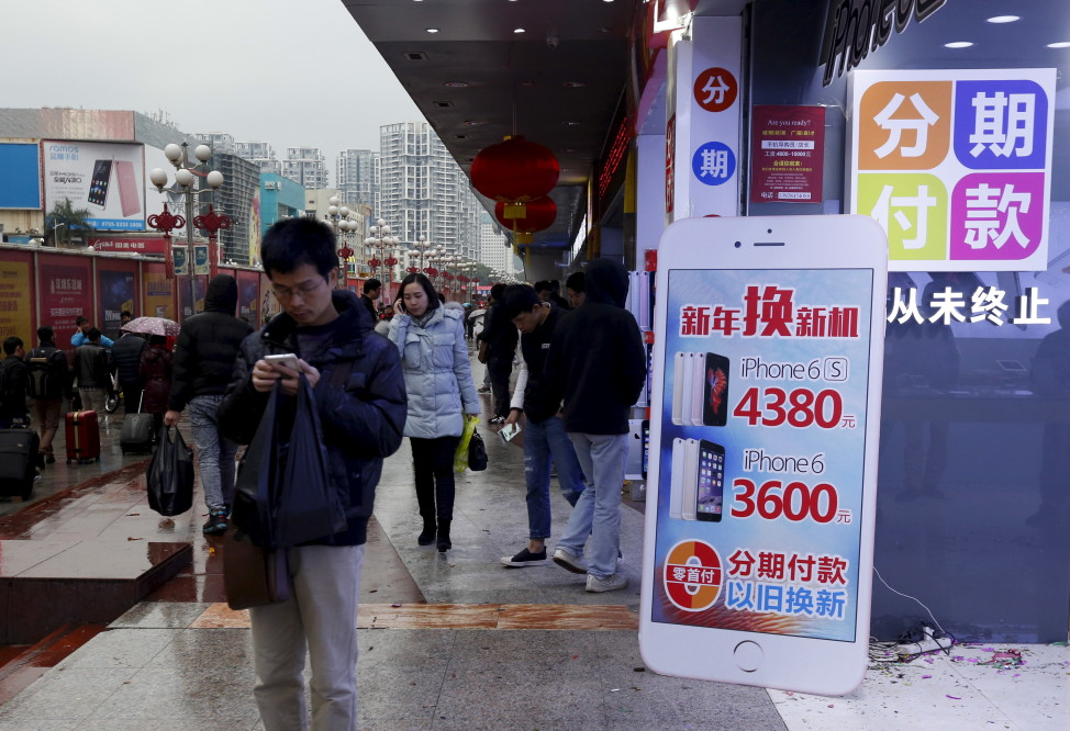 A man checks his smartphone outside a store promoting the Apple iPhone products in the southern Chinese city of Shenzhen, Jan. 26, 2016. (Reuters)