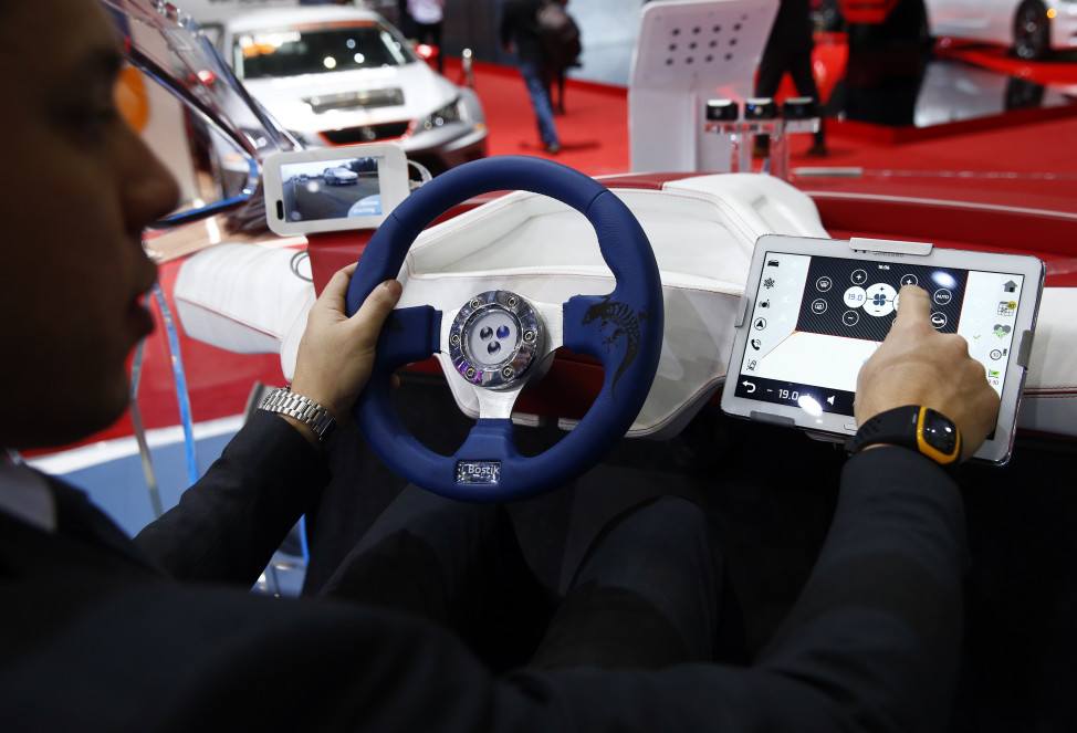 FILE - An employee sits inside a virtual reality connected car cockpit built by Segula Technologies during the first press day ahead of the 85th International Motor Show in Geneva, Switzerland, March 3, 2015.  (Reuters)