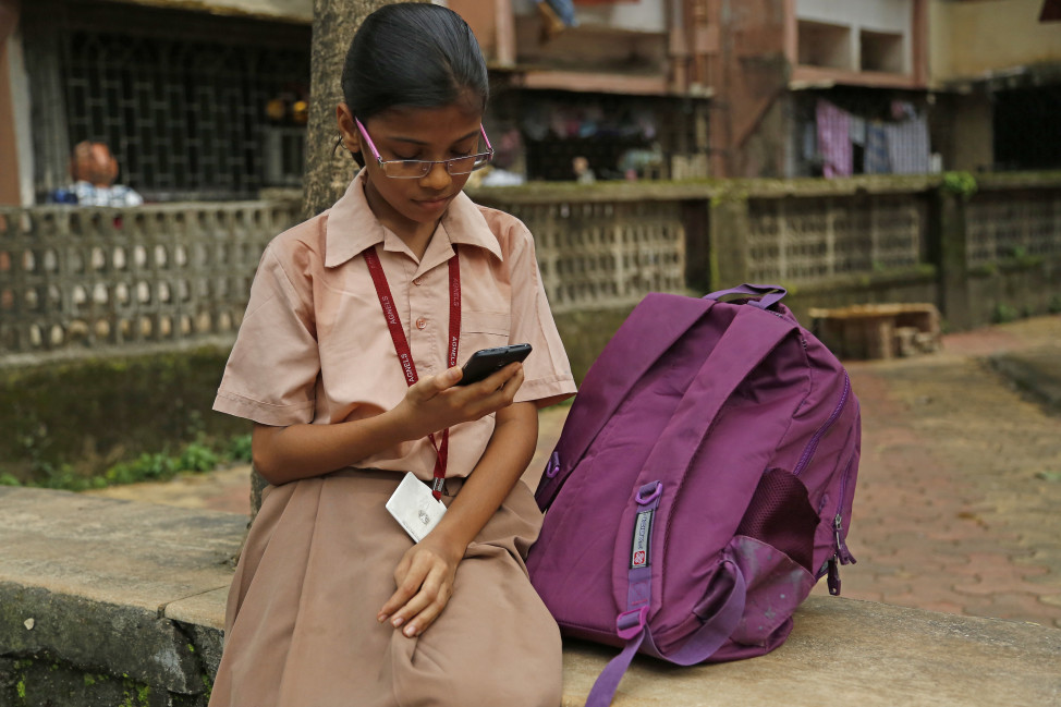 Amisha Vittal Khedekar, a student reading outside her school in India. (Worldreader)
