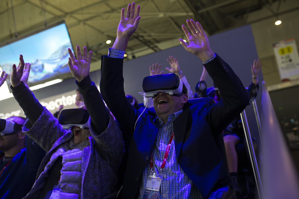 People react as they use the new Samsung Gear 360, a 360-degree camera, during the Mobile World Congress Wireless show in Barcelona, Spain, Feb. 24, 2016. Many companies unveiled their latest virtual reality (VR) headsets and related content as the technology dominated  this year's event. (AP)