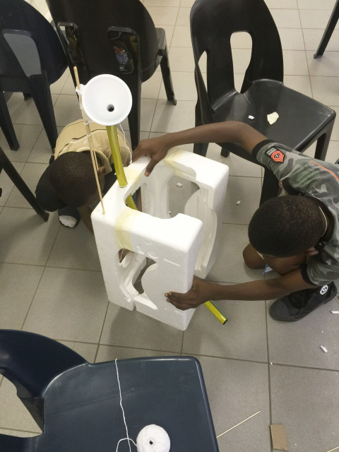 'Design Squad Global' kids at the Phatsimong Youth Center in Gaborone, Botswana build a mouse trap-inspired pill dispenser. The contraption is meant to help kids remember to take their pills in a country with a high prevalence of HIV/AIDS. (WGBH Educational Foundation)