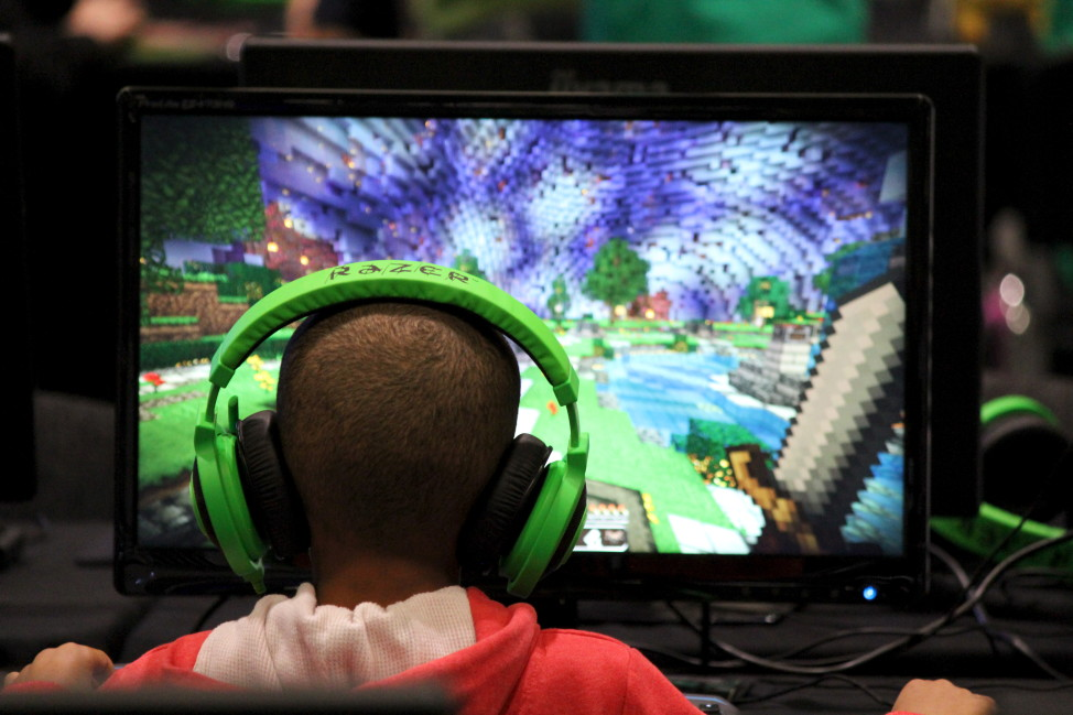 FILE - A child plays the Minecraft video game at the Minecon convention in London, Britain, July 4, 2015. Minecraft is a blocky world that lets players mine for resources and build elaborate structures, among other activities. (Reuters)