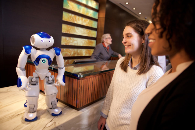 This photo, distributed by Feature Photo Service for IBM, shows visitors to the Hilton Hotel in McLean, Va. meeting the robot concierge  'Connie', named after Conrad Hilton and powered byIBM Watson and WayBlazer.  Connie uses cognitive computing and machine learning to answer questions posed in natural language while learning from the interactions. (AP/Green Buzz Agency/Feature Photo Service for IBM)