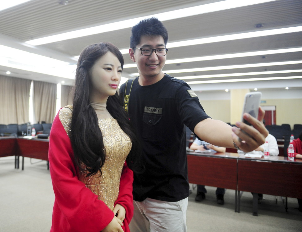 A man takes pictures with humanoid robot Jiajia produced by University of Science and Technology of China, at Jiajia's launch event in Hefei, Anhui province, April 15, 2016. Jiajia can converse with humans and imitate facial expressions, among other features. b (Reuters/China Stringer Network)