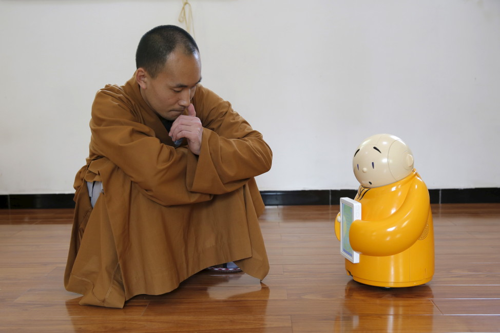 Master Xianfan looks at robot monk Xian'er as he demonstrates the robot's conversation function during a photo opportunity in Longquan Buddhist temple on the outskirts of Beijing, April 20, 2016. (Reuters)