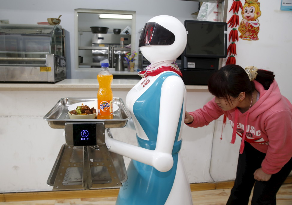 A woman inputs orders for a robot which works as a waitress in a restaurant in Xi'an, Shaanxi Province, China, April 20, 2016. (Reuters/China Stringer network)