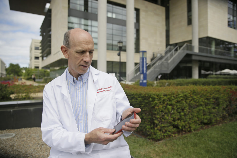 File - Dr. Michael V. McConnell, a cardiologist who uses an app to study heart disease, poses with his smartphone outside the Stanford Medical School in Stanford, California, July 7, 2015. Scientists like McConnell who are overseeing studies that use specialized iPhone apps say they have the potential to transform medical research by helping them collect data routinely from far more people than usually participate in health studies. (AP)
