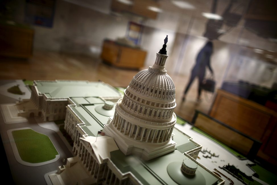 A woman walks by a miniature of the Capitol building at the Hart Senate Office Building at Capitol Hill in Washington, Jan. 20, 2016.