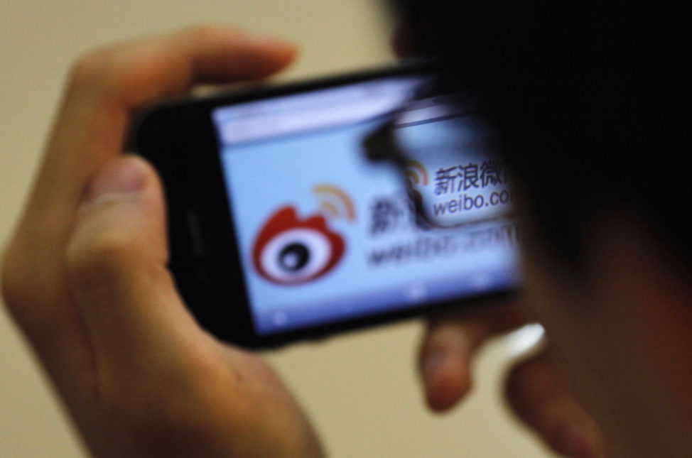 FILE - A man holds an iPhone as he visits Sina's Weibo microblogging site in Shanghai, China. (Reuters)