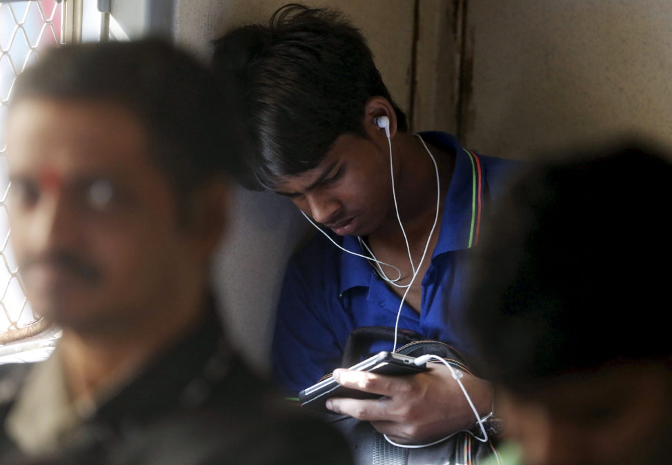 FILE - A man watches a video on his mobile phone as he commutes by a suburban train in Mumbai, India, March 31, 2016. (Reuters)