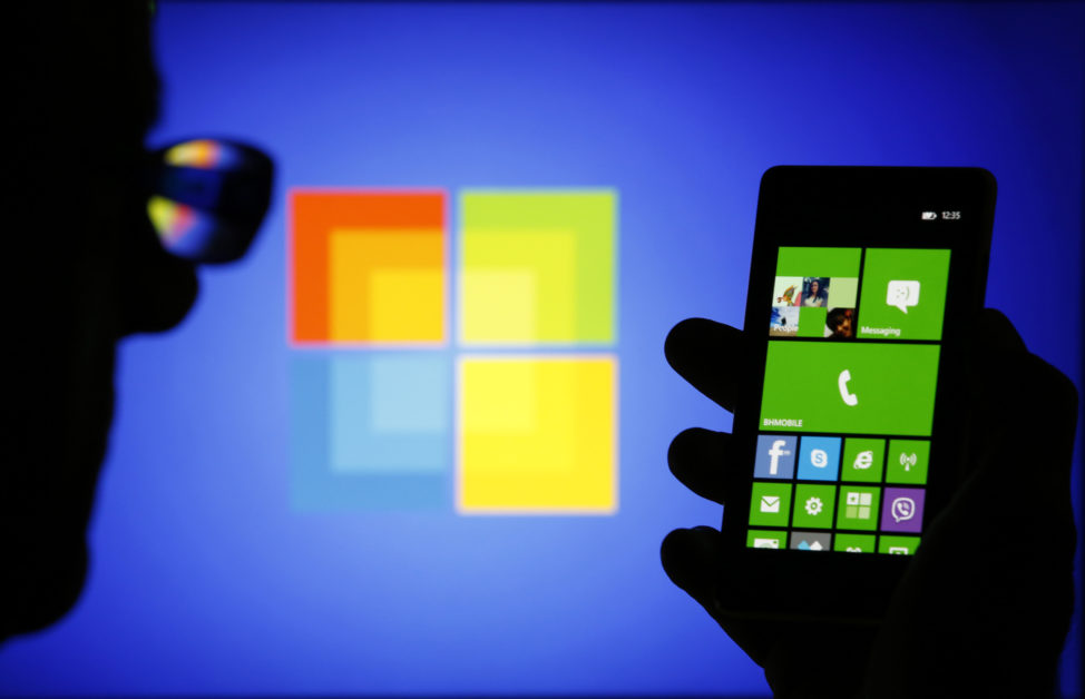 FILE - A man is silhouetted against a video screen poses with a Nokia Lumia 820 smartphone in this photo illustration taken in Zenica, Bosnia.