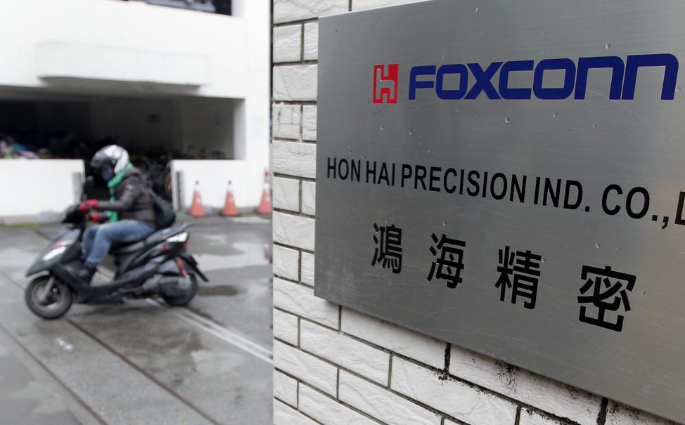 A motorcyclist rides past the entrance of the headquarters of Foxconn, in Tucheng, New Taipei city. Taiwan. (Reuters)