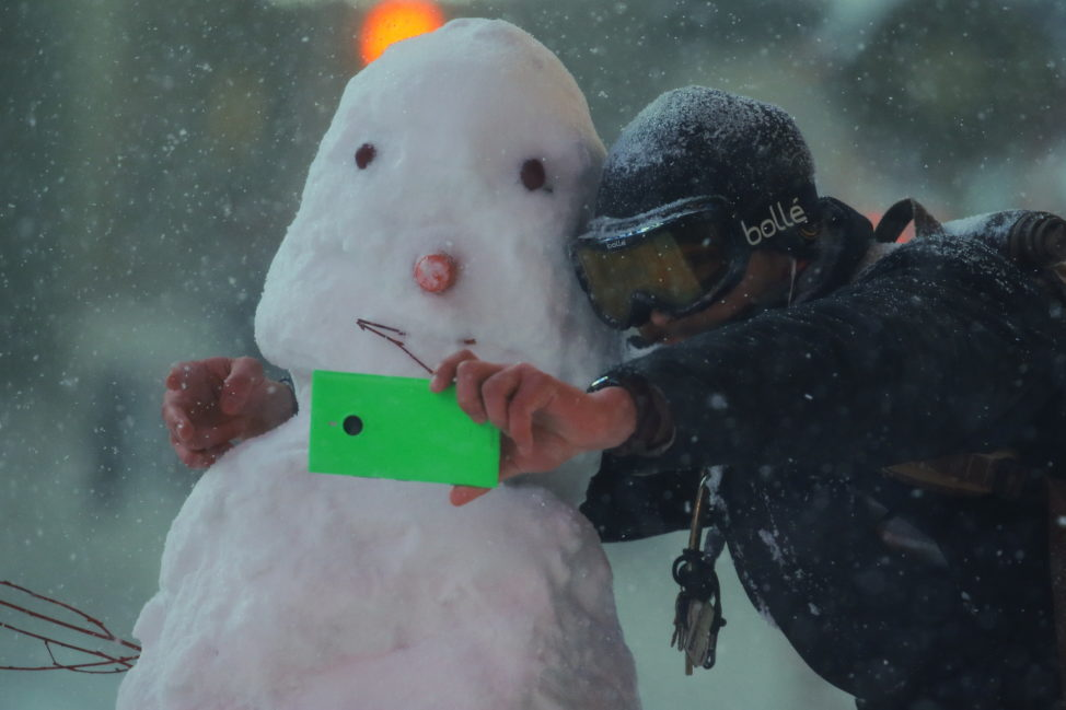 A man takes a selfie with a snowman during a snow storm in Times Square in the Manhattan borough of New York, Jan. 23, 2016. (Reuters)
