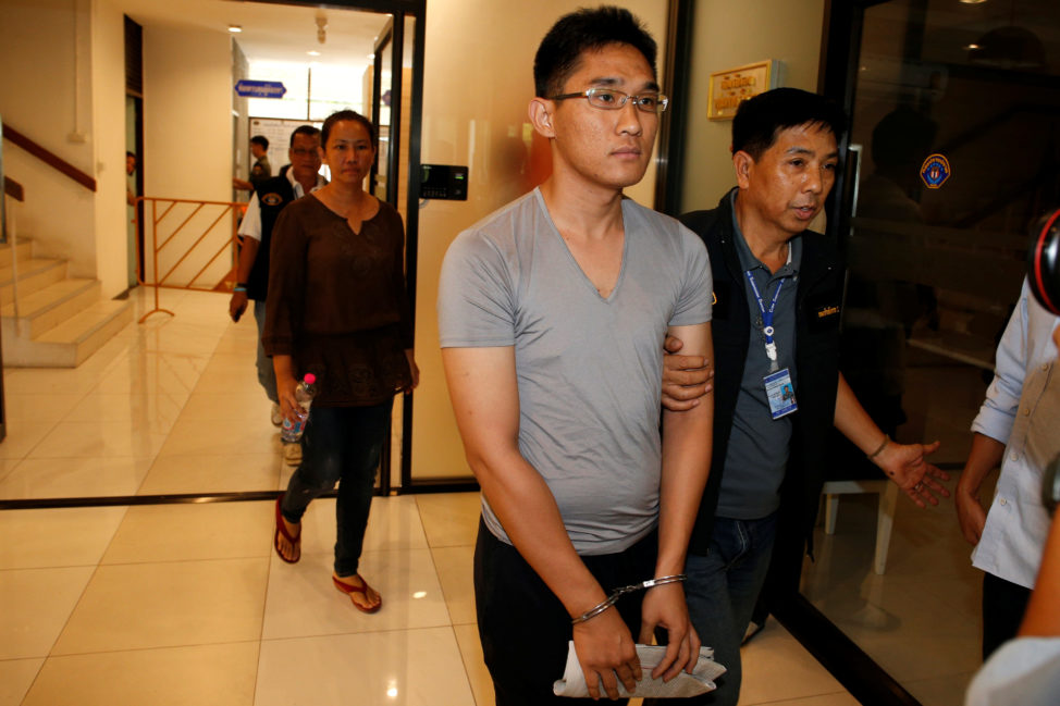Harit Mahaton (C) and Natthika Worathaiyawich (rear), two of eight activists who were jailed after posting critical comments on Facebook, arrive to a crime suppression division after being charged with violating the royal defamation law, in Bangkok, Thailand, May 11, 2016. (Reuters)